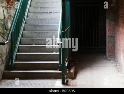 Garde-corps vert Cave Ville escaliers menant à la pierre et la brique de niveau inférieur Banque D'Images