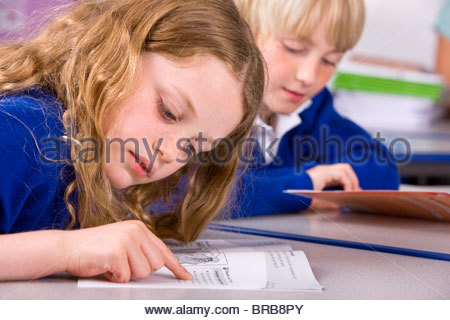 Fille de l'école cahier lecture in classroom Banque D'Images
