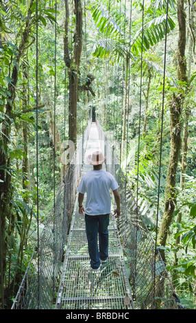 L'homme marchant sur pont suspendu dans la forêt tropicale,, la Fortuna, Arenal, Costa Rica, Amérique Centrale Banque D'Images