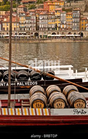 Tonneaux de vin de port sur un bateau sur le fleuve Douro à Vila Nova de Gaia dans l'arrière-plan, Porto, Portugal Banque D'Images