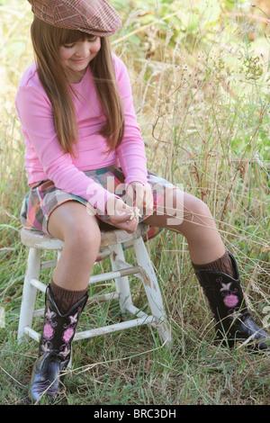 Jeune fille assise sur un tabouret de porter un chapeau et des bottes de cow-boy; Troutdale, Oregon, United States Banque D'Images