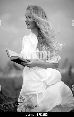 Fille en robe blanche tenant un livre Banque D'Images