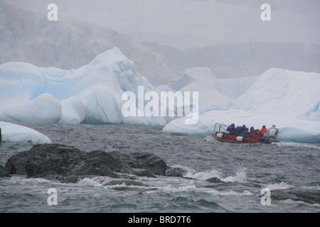 Les touristes en zodiac au large entre les icebergs, Cuverville Island, Antarctica Banque D'Images