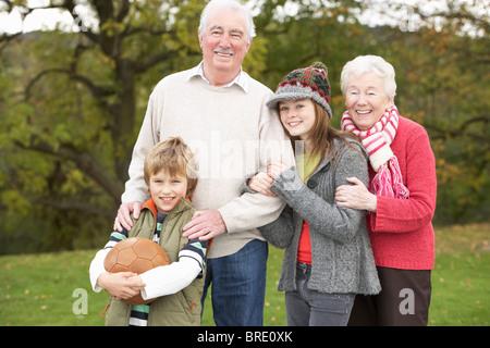 Les grands-parents avec petits-enfants Holding Football extérieur Banque D'Images