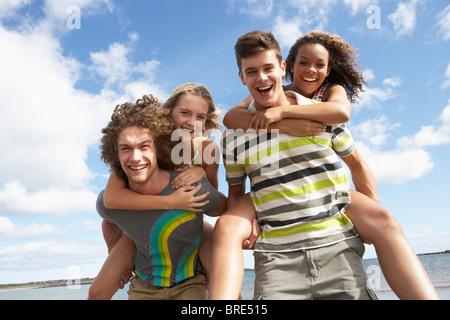 Groupe de jeunes amis s'amusant sur l'ensemble de plage en été Banque D'Images