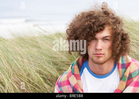 Young Man Standing In Sand Dunes enveloppé dans le contrat cadre Banque D'Images