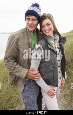 Jeune couple en train de marcher à travers les dunes de sable portant des vêtements chauds Banque D'Images