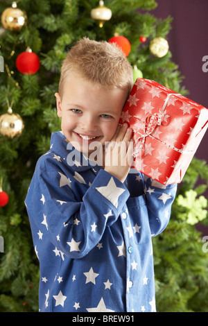 Young Boy Holding Wrapped Present in front of Christmas Tree Banque D'Images