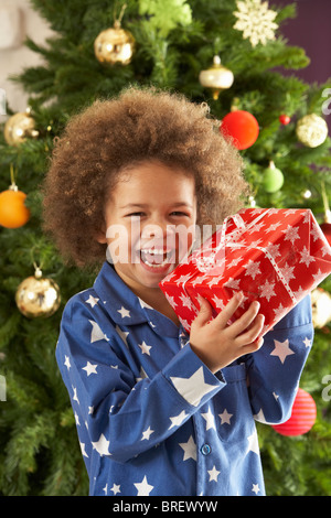 Young Boy Holding Gift in front of Christmas Tree Banque D'Images