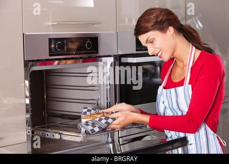 Attractive young woman en tenant son cake maison du four Banque D'Images