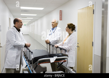 Doctors talking in hospital corridor Banque D'Images