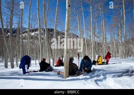 Cinq hommes assis dans la neige et de peuplier faux-tremble au dîner tandis que sur un voyage de ski en arrière Banque D'Images