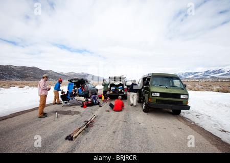 Six hommes de traîner dans le milieu d'une route avec leur équipement de ski et des véhicules dans une zone montagneuse Banque D'Images