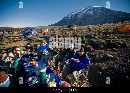 Une équipe de randonneurs ont un bon petit déjeuner au lever du soleil d'environ 1000 ft. En dessous du sommet du Banque D'Images
