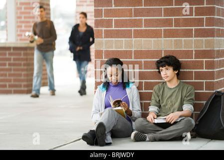 Étudiants assis ensemble sur le trottoir en dehors de l'école