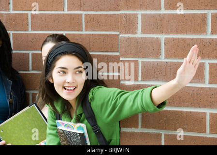 Teenage girl waving to friend Banque D'Images