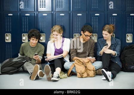 Les élèves du secondaire à traîner, assis sur le plancher par les casiers