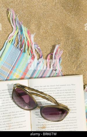 Un livre sur les lunettes et la serviette sur la plage Banque D'Images