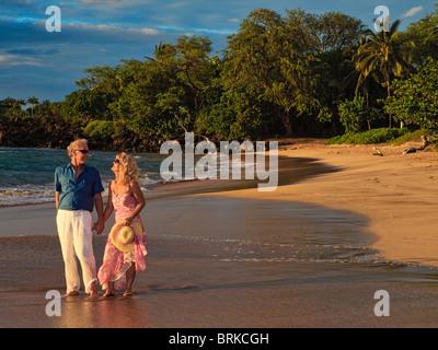 Couple sur une plage au coucher du soleil maui Banque D'Images