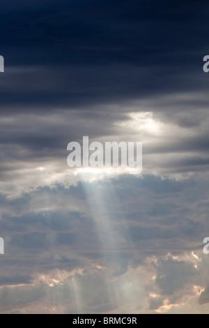 Soleil qui brille à travers les nuages sombres Banque D'Images