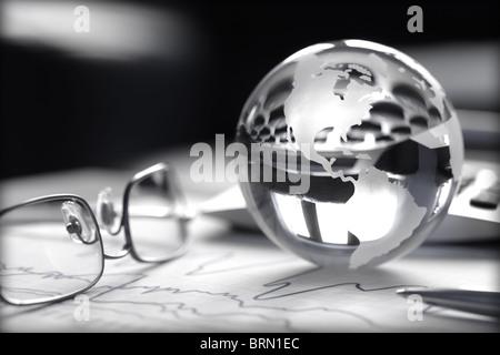 Image globe de verre aux couleurs de graphiques boursiers avec, calculatrice et spectacles Banque D'Images
