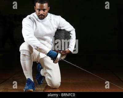 Portrait d'un tireur portant des uniformes d'escrime et de tenir une épée dans un gymnase sur fond noir Banque D'Images