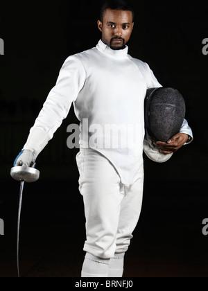 Portrait d'un tireur portant des uniformes d'escrime et de tenir une épée et un masque isolé sur fond noir Banque D'Images