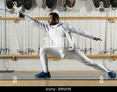 Tireur en blanc uniforme escrime pratiquer dans une salle de sport Banque D'Images