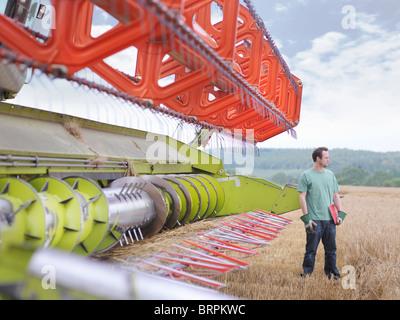 Agriculteur et combine harvester Banque D'Images