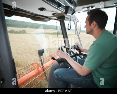 Farmer driving combine harvester Banque D'Images
