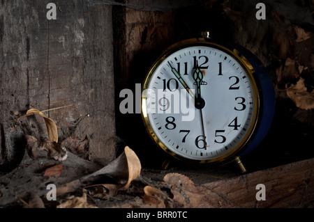 Temps passé concept - vieux réveil oublié sur une étagère avec des feuilles et d'araignées. Banque D'Images