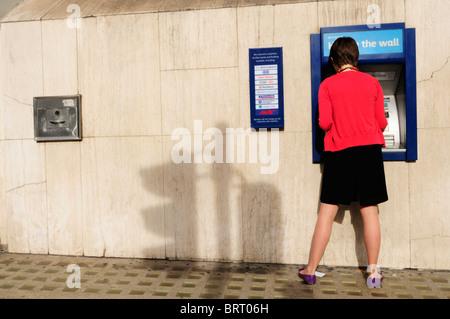 Une jeune femme retire de l'argent à partir d'un trou de la Barclays Bank dans le mur Cash Machine ATM, London, England, UK