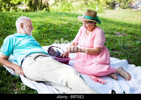 Senior couple bénéficie d''un pique-nique romantique dans le parc. Banque D'Images