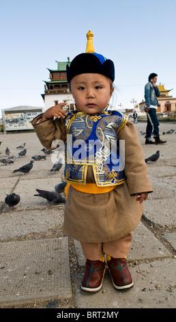Un mignon petit garçon mongol habillé en vêtements traditionnels. Banque D'Images