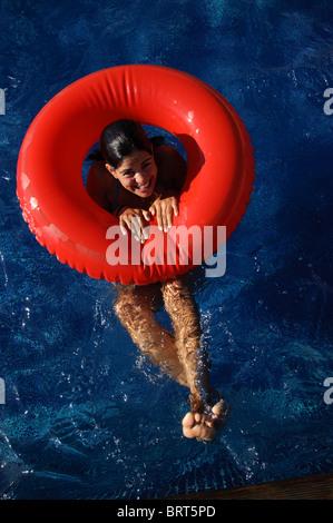 Jolie jeune femme de race blanche dans une piscine avec lilo rouge d'en haut Banque D'Images