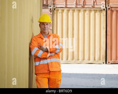 Portrait of mid adult worker standing près de conteneurs de fret et à la recherche à l'appareil photo. Vue avant, de forme horizontale, copy space Banque D'Images