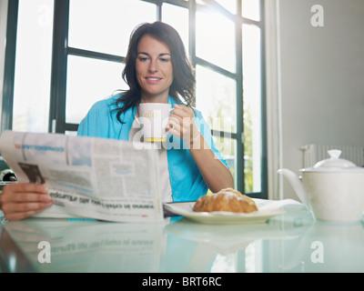 Mid adult woman drinking coffee et la lecture des nouvelles. De forme horizontale, copy space Banque D'Images