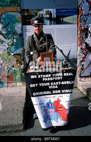 Vendeur de souvenirs dans un uniforme de garde-frontières vend des timbres de passeport de la RDA en face d'un morceau Banque D'Images