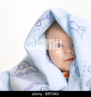 Cute little boy expressive couverts par soft couverture bleue isolé sur fond blanc. Banque D'Images