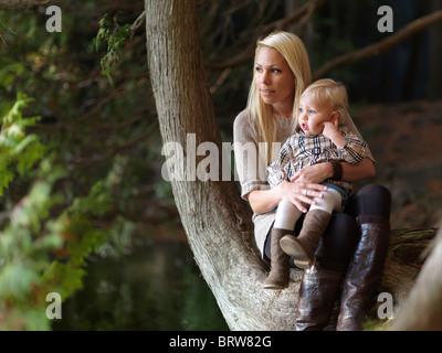 Jeune mère avec une fille qui a deux ans, assis à un lac dans la nature. L'Ontario, Canada. Banque D'Images