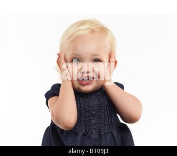 Portrait d'une fillette de deux ans faisant un drôle de visage isolé sur fond blanc