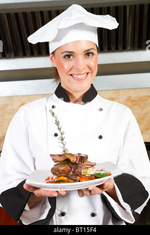 Belle jeune femme chef presenting food in kitchen Banque D'Images