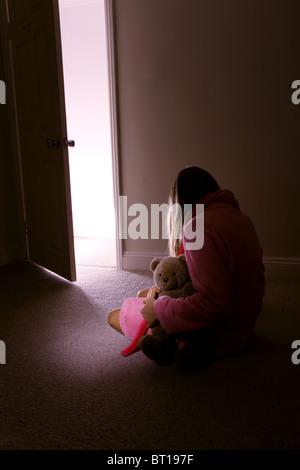 Petite fille seule dans une pièce sombre holding a teddy bear, vue arrière. 5 Banque D'Images