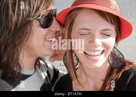 Close up of teenage boy whispering in smiling girl's ear Banque D'Images