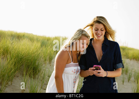 Smiling teenage girls text messaging with cell phone on beach Banque D'Images