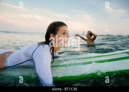 Caucasian woman paddling on surfboard in ocean Banque D'Images