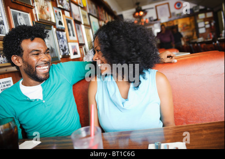 Smiling couple sitting in diner booth Banque D'Images