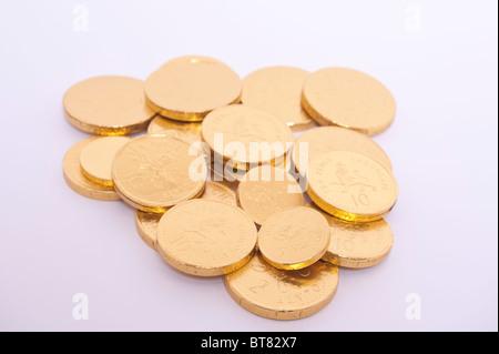 A la photo en gros plan de quelques pièces d'or au chocolat sur un fond blanc. Banque D'Images