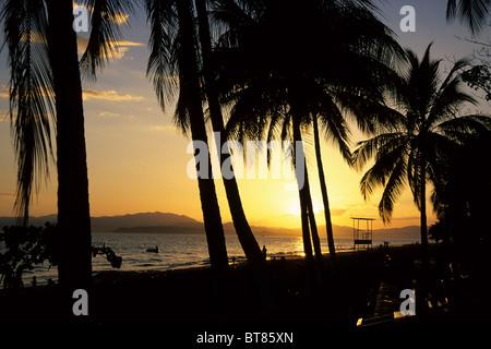 Plage avec des palmiers, coucher de soleil sur la côte du Pacifique à Puntarenas, Péninsule de Nicoya au dos, le Banque D'Images