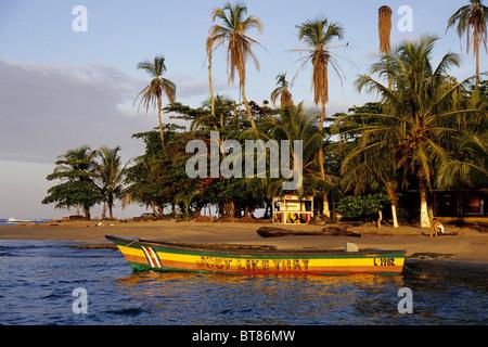 Petit bateau peint en couleurs reggae sur une plage tropicale avec palmiers, Puerto Viejo de Talamanca sur la côte Banque D'Images